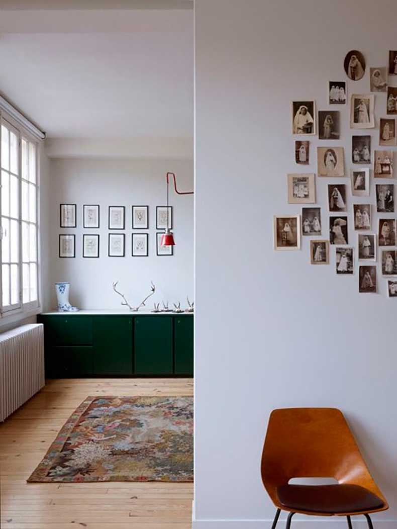 a-kitchen-with-green-cabinets-and-a-wall-of-old-photos