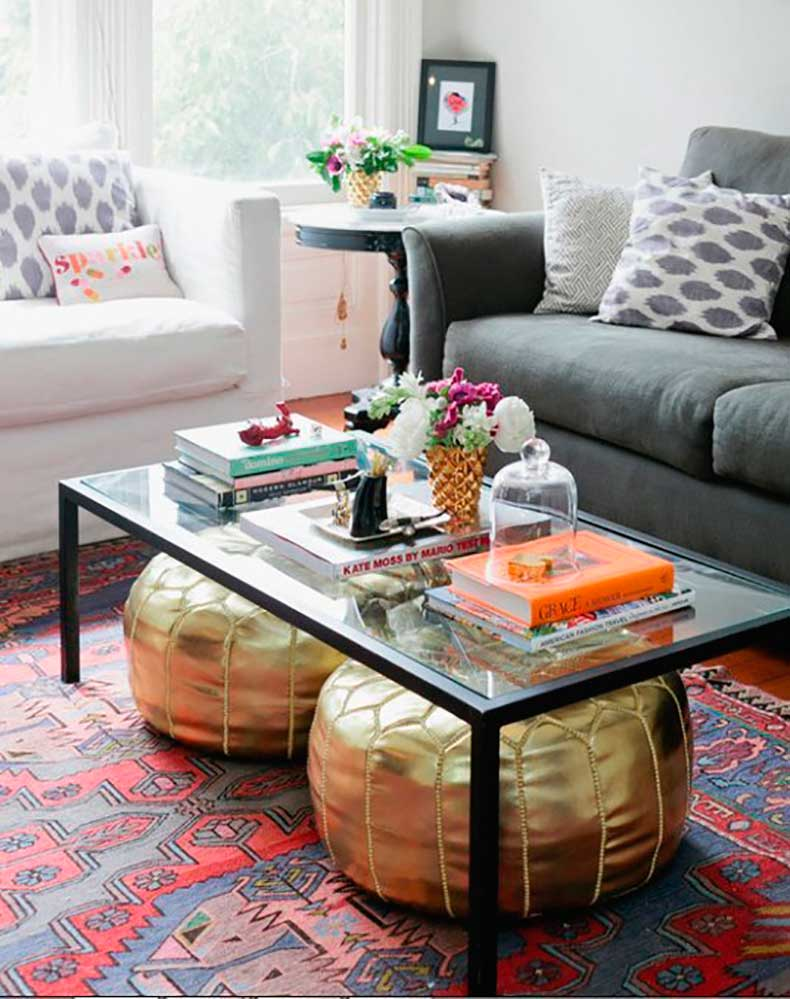 two-gold-poufs-under-a-glass-coffee-table-in-a-living-room