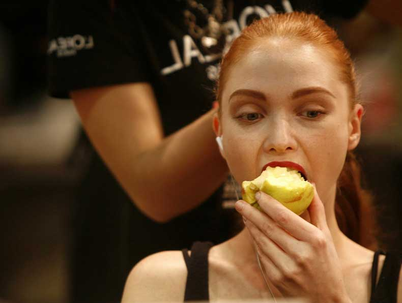 a-redheaded-model-enjoys-an-apple-as-her-hair-is-styled-backstage-at-antonio-pernas-madrid-show