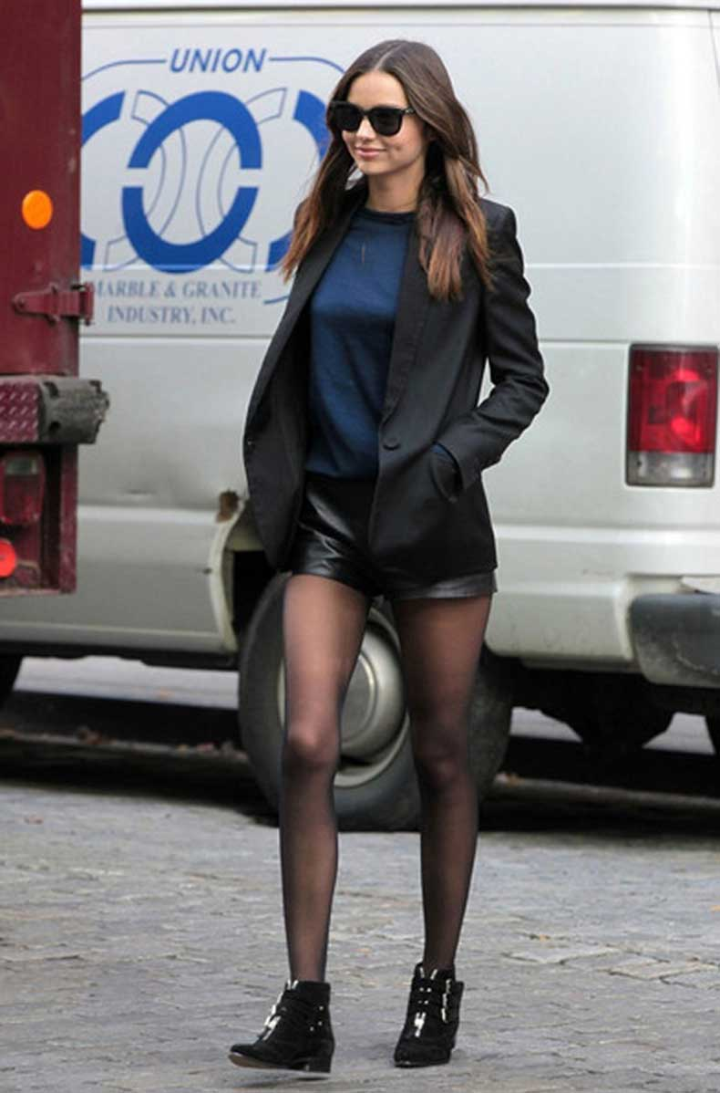 candid-Miranda-kerr-street-style-black-leather-shorts-sheer-pantyhose-flat-black-ankle-boots-blue-shirt-grey-blazer-simple-style-cool-sunglasses.jpg