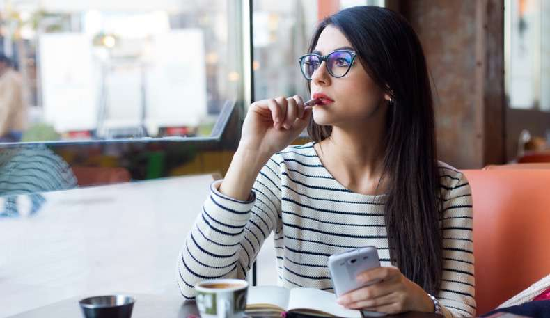 Portrait of young beautiful woman using her mobile phone in coffee.