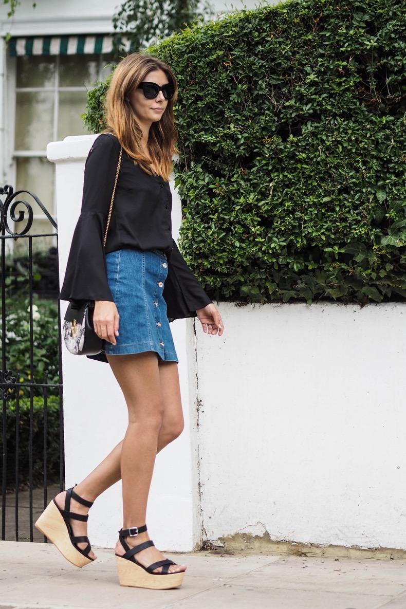 EJSTYLE-wears-bell-sleeve-black-shirt-button-down-denim-skirt-wedge-sandals-chloe-drew-snakeskin-dupe-bag-70s-inspired-outfit-OOTD-street-style