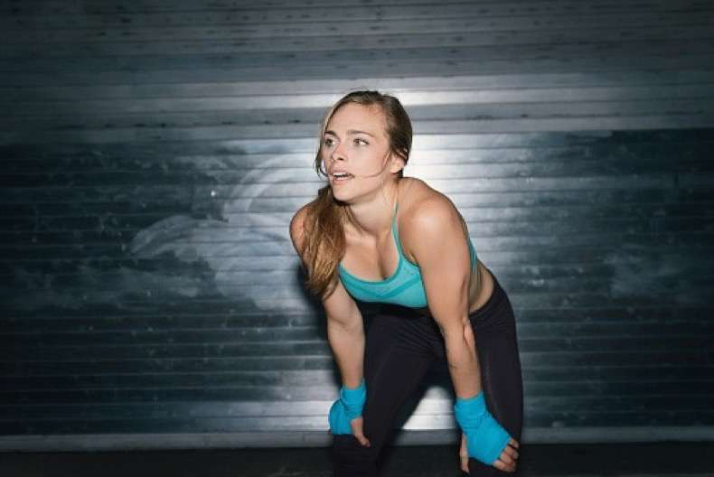Young woman, working out, hands on knees, outdoors, at night