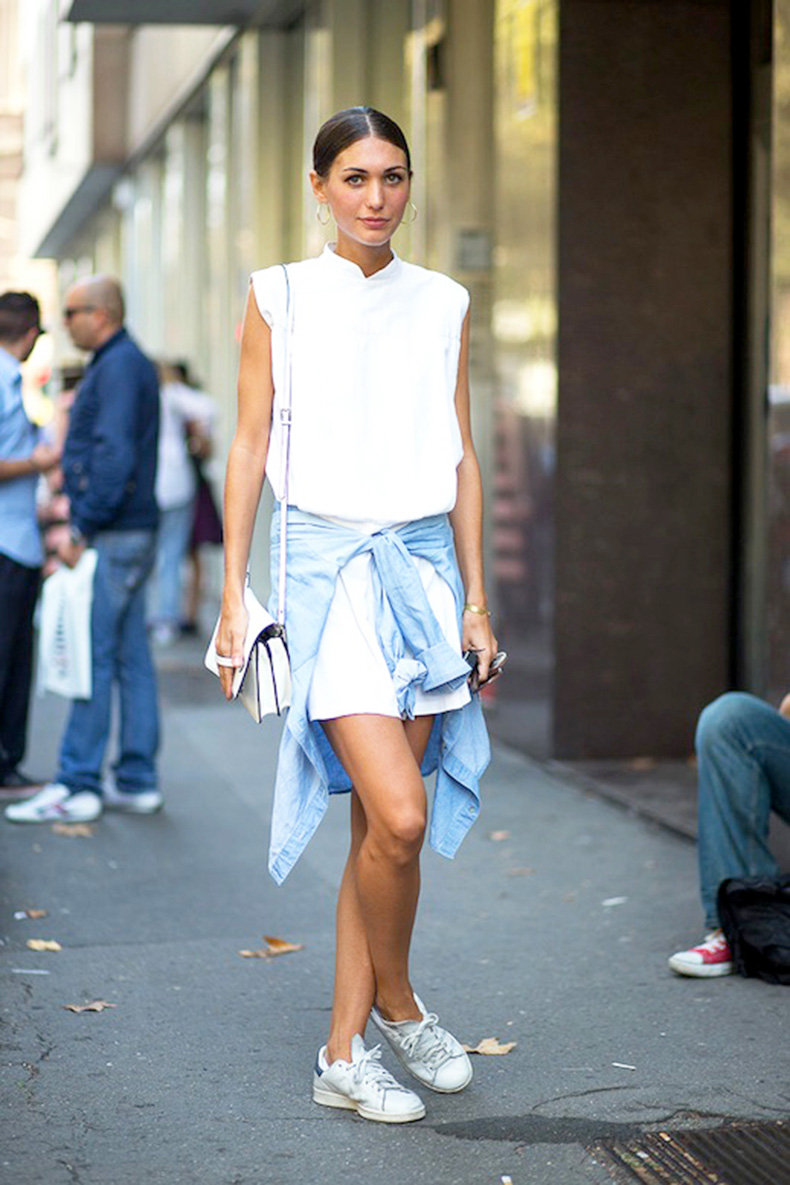 le-fashion-blog-street-style-mfw-white-sleeveless-shirtdress-crossbody-bag-denim-jacket-tied-around-the-waist-sneakers-easy-summer-look-via-harpers-bazaar