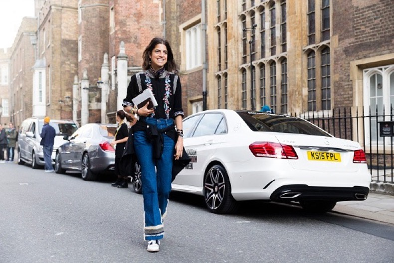 LONDON, ENGLAND - SEPTEMBER 19:  Leandra Medine of Manrepeller enters the Simone Rocha in a black embroidered floral turtleneck, Racil jacket around her waist, high waisted flaired jeans, and oxford shoes during London Fashion Week Spring Summer 2016 on September 19, 2015 in London, England  (Photo by Melodie Jeng/Getty Images)