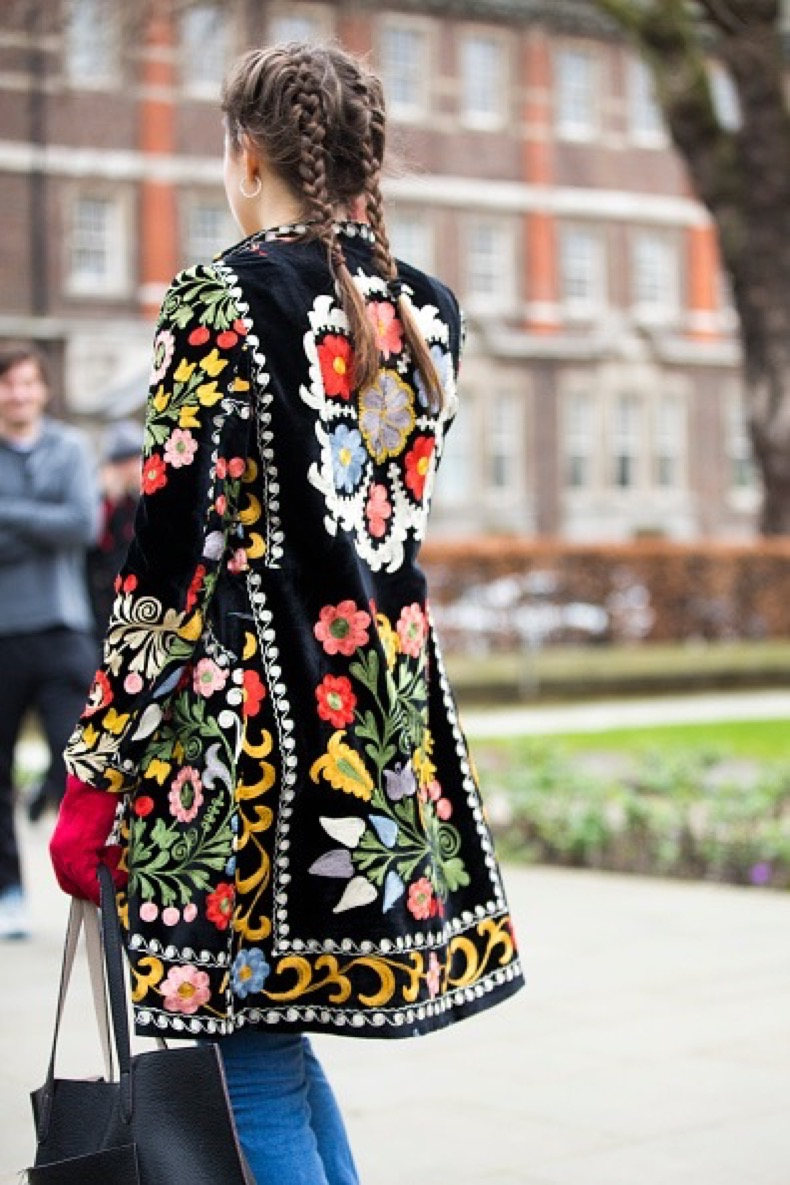 A showgoer wears her hair in two french braids and wears a floral embroidered jacket at the Topshop show at Tate Britain during London Fashion Week Autumn/Winter 2016/17 on February 21, 2016 in London, England.