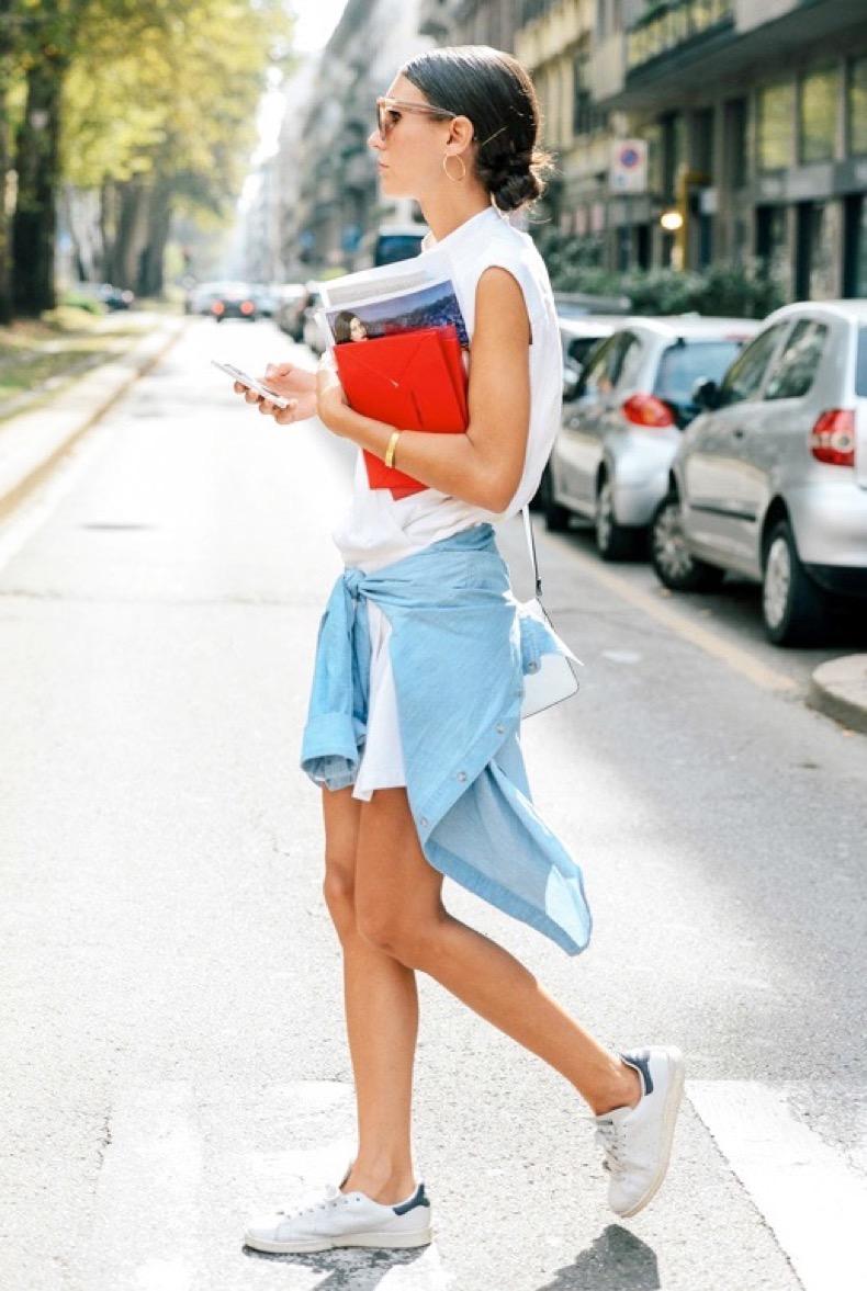 le-fashion-blog-laid-back-street-style-low-bun-hoop-earrings-white-sleeveless-shirtdress-denim-shirt-tied-around-the-waist-adidas-stan-smith-sneakers-via-vogue